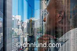 This stock photo explores the themes of decisions and leadership in business by showing an executive contemplating an urban high rise environment using multiple exposures to add drama and interest.