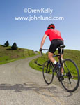Photo of a cyclist riding uphill on a country gravel road. Beautiful clear blue sky.  Lush green grass hillsides.  Stock photo of a man riding a bicycle in the country. The man is wearing cycling gear, helmet, gloves etc.