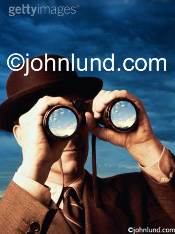 Stock photo of a derby hat wearing business man looking through binoculars searching for a brighter future.