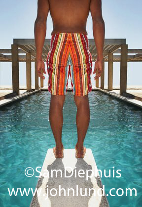 Picture of a man on a diving board from the shoulders down. The man is wearing bremuda shorts and standing at the leading edge of the board.  Striped shorts. Clear blue water. Hot summer day.