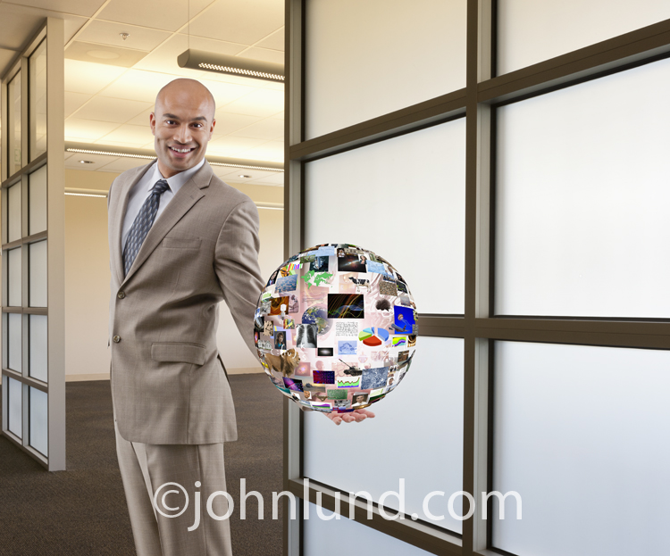 Photo of a businessman holding out a futuristic globe of images in a corporate office setting.