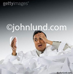 Stock photo of a business man in a pile of adding machine tape and holding his head in disbelief at the numbers he is seeing.