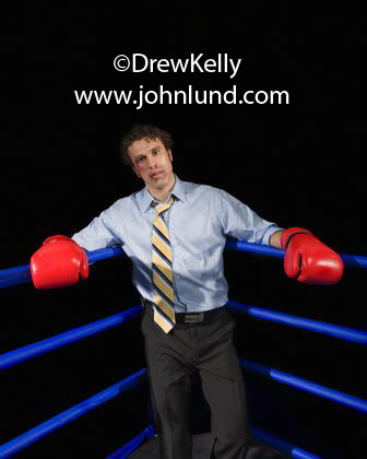 Funny stock photo of a businessman in a dress shirt, tie, and slacks and wearing boxing gloves in the corner of a boxing ring. The businessman is on the ropes.  Ad pics of beat up businessmen. Man with a black eye. Funny advertising picture.