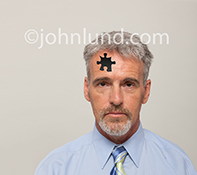 A man is missing cognitive function in this stock photo showing a confused looking man with a puzzle shaped piece missing from his forehead...a metaphor for such concepts as Alzheimers, dementia, and mental disorders.