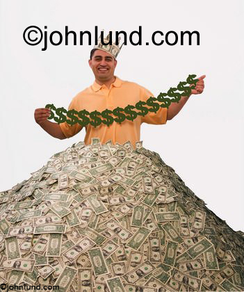 An Hispanic man stands in a huge pile of money or currency and holds up paper dolls cut from dollar bills. He his happy and has a crown on his head made from more money.
