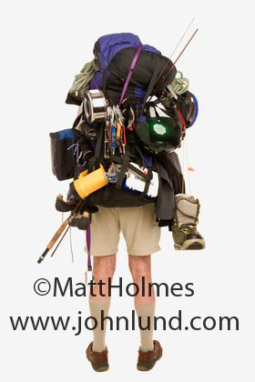 Hilarious funny pictue of a person wearing a huge load on his back for his hiking and camping trip. He has everything on his back except the kitchen sink. Fishing pole, water, boots, backpack. Funny advertising pictures.