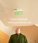 Photo of a man in an office hallway standing and looking up at a green exit sign attached to the ceiling right over his head. Man is wearing green shirt and glasses and the shot is a low angle.