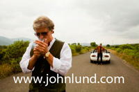 A well dressed senior man lighting his cigarette while standing in the middle of the road.  His wife and broken down car are in the background.