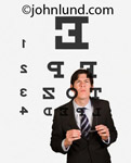 Picture of a businessman squinting to read an eye chart. The man is holding a pair of eye glasses in his hands. The eye chart is transparanet with the man facing the camera which is looking through the eyechart at the businessman.