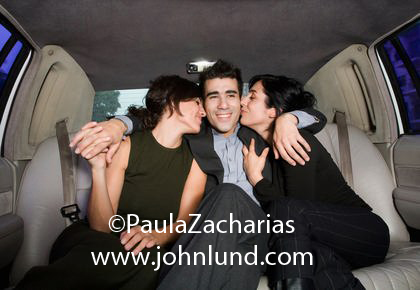 Picture of two women are kissing this handsome Latino man in the back of the limousine.  One lady friend on each side and he has his arms around both. Women dressed in black with a man in a limo. Advertising photography.