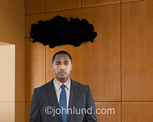 A man stands glumly under a black cloud in a high-end office setting in this stock photo about depression and business problems.