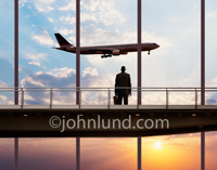 A man with a briefcase stands on a walkway at an airport and watches an airliner fly by either in a landing approach or taking off.