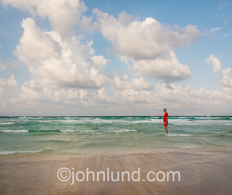 A man wearing a red shirt and red bathing suit stands in shallow water on a tropical beach gazing into the distance under a sky filled with light, puffy clouds in an image about serenity, tranquility, solitude, and travel.