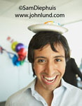 Pictures of funny people. This hispanic man is being silly at the office party. He has a piece of cake from the party on a paper plate balanced on the top of his head. Silly office pics.