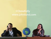 Stock photo representing global communications.  A man is on the phone at a desk and a woman is on another phone at a second desk which butts up to the first desk. The desks are straddled by a world globe.  Mans background is yellow.