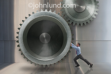 A working man in business attire struggles to push a huge gear in a  metaphorical photo about making things work.