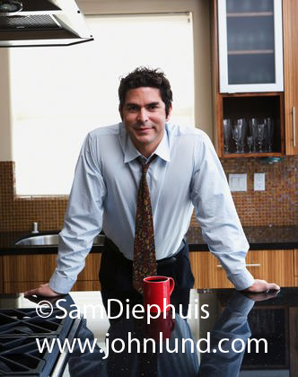 Picture of a hispanic businessman leaning on the counter in his kitchen with a red cup of coffee in front of him on the counter. Dress shirt and tie.
