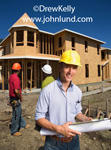Picture of a smiling young architect wearing a yellow hard hat and holding a clipboard and a set of blueprints.  Construction workers in hard hats in the background. Outdoor pictures of new construction projects.
