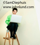 Funny picture of a man sitting atop wooden ladder working on his laptop.  Funny picture of a man perched atop a step ladder using his laptop computer. Funny business pics.