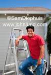 A man holding a paintbrush  and leaning on a ladder while looking at the camera. He is happy and smiling as he goes about his home improvment project. House painter pictures.