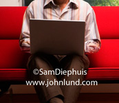 Image of a man using a laptop on an orange sofa. The man's face is not in the picture, torso only. Man is wearing striped shirt. Ad pics.