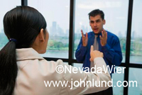 Picture of business people arguing in an office. She has her back to the camera and is pointing her finger at the other business person, a man who is gesturing with his hands. Business people arguing pics.
