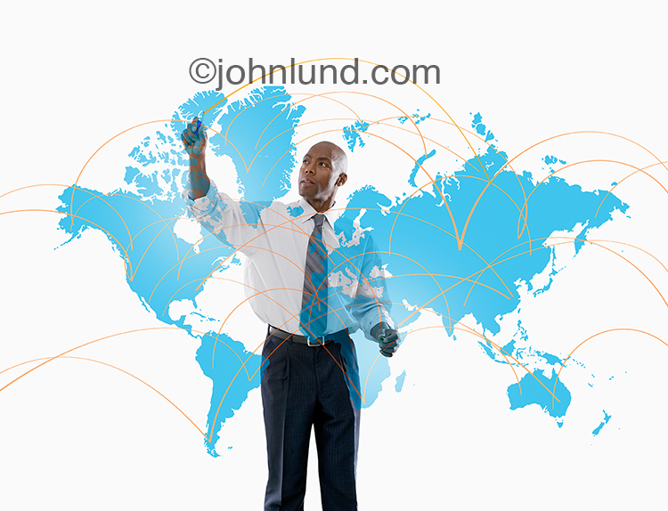 Global business strategy is being mapped out by an African American businessman in this stock photo featuring a map of the continents with connecting lines being illustrated by an executive.