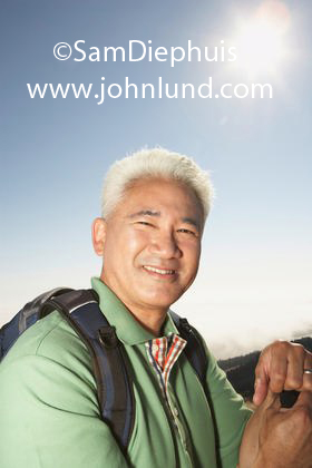 A mature Japanese or Chinese man is wearing a backpack on a day hike under a bright blue sky in Northern CA.  He is wearing a green shirt and the sun is behind and above him.