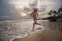 Photo of a mature, fit woman running on a tropical beach at sunset. She is jogging along the surf line as the sun sets behind her.