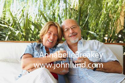 Two old people sitting on a swing in the garden drinking glasses of wine. Senior couple laughing together and enjoying wine together. He is bald and has a gray goatee.