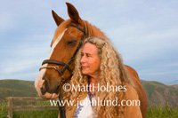 Picture of a senior mature woman with her prized horse. Photo of a woman with her horse. Horse is wearing bridle and is brown with a white face. In the foothills with a blue sky.
