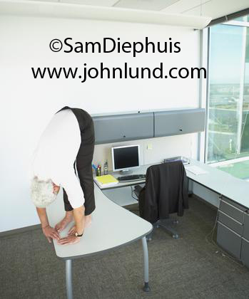 Pic of a senior man bending sharply at the waist and standing on a desk in his office. Possibly doing a yoga position, or maybe just stretching. Strand pics for business ads.