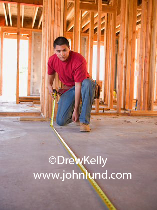 Mexican Or Latino Construction Worker Using Tape Measure In Home Under