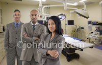 In this picture three executives stand, in business attire, in an operating room representing the support people behind the scenes in the medical industry.