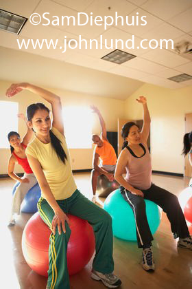 A group of people, mostly women, are taking an exercise class and using exercise balls in their routine. The women are sitting on the balls with one arm up over their heads and the other hand on their thighs.