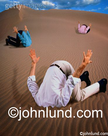 Stock photo of three men with their heads in the sand like Ostriches Hiding In Fear From The Challenges Of Change.