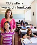 Pictures of kids and teachers in middle school.  Stock photo for advertising showing a female teacher standing behind her young female asian student and both are smiling at the camera.  Kids in class studying in the background.