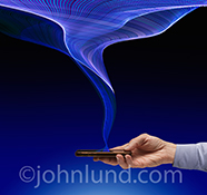 Mobile networking connection is the primary concept behind this stock photo of a mobile device connected to a network via a swirling, expanding web of blue light trails showing data transmission, big data, and wireless connections.