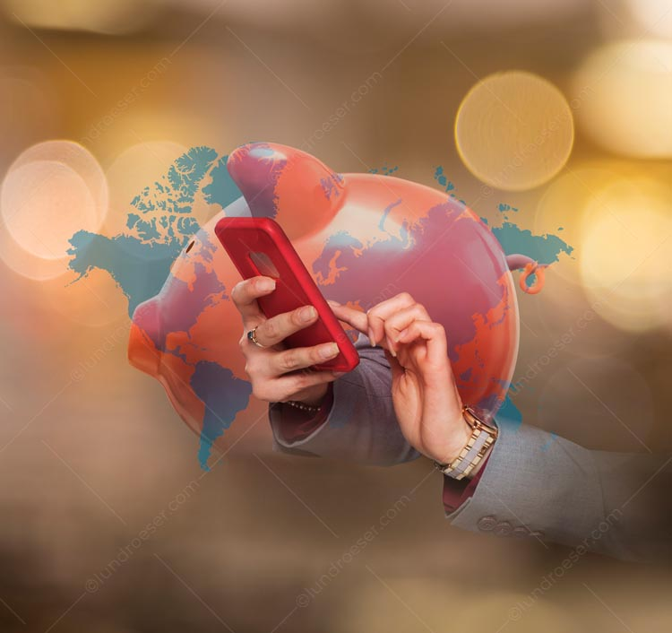 A piggy bank, a global map, and hands using a smartphone are multiple exposed in this piggy bank stock photo about global mobile banking.