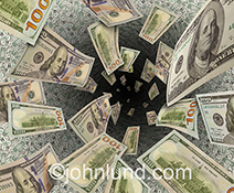 Money down the hole, or wasted money, is seen in this stock photo of hundred dollar bills disappearing into a black hole.