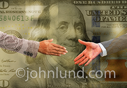A pair of hands are about to shake against a backdrop of a hundred dollar bill in a stock photo about business teamwork, finance, and investment.