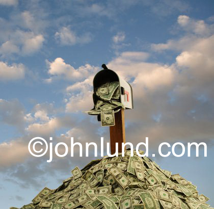 A mail box juts up from a big heaping pile of money. Cash is falling from the open mailbox. Cloudy blue sky background.