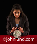 Picture of a young gypsy fortuneteller with a cyrstal ball full of cash money.  Visible in the glass ball are dollar bills.  Predicting the future value of your investments. Money pics.