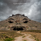 This monster mountain image literally has a monster's face created from the terrain of the mountain side with a road leading up into its cavernous mouth in a metaphor for evil, fearsome, and scary aspects of the natural world.