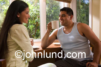 Picture of a happy smiling hispanic couple having coffee together at home in the morning. Latino woman with long black hair. Latino man with short black hair. Sitting in front of a large window.