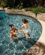 Mother and daughter playing in a swimming pool. A young girl is jumping into the swimming pool and her mother is in the pool ready to catch her.