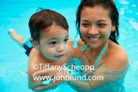 Hispanic mother or teacher teaching a young child how to swim in the swimming pool.  Both teacher and child are smiling.  Swimming photos.