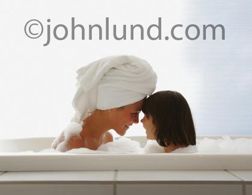 A mother and her daughter are nose-to-nose in a bath tube full of bubbles in a touching picture of motherhood and child rearing.