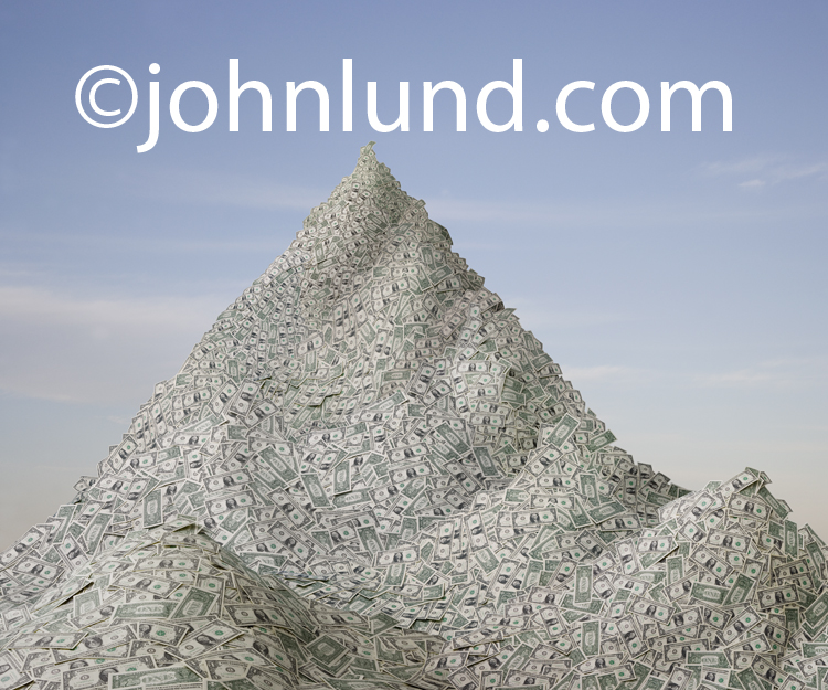 A huge mountain of money in the form of a giant pile of dollars looms up against a hazy sky in this stock photo about savings, success, finance and abundance.