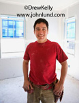 Picture of a mudder.  Happy young man wearing a toolbelt, orange T-shirt , brown pants, and smiling.  Picture of new hung sheetrock in a new or remodeled home. Advertising picture for new homes and remodeling services.